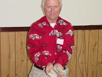 Ron shows the $250 a luvky winner will receive from the 50/50 drawing.